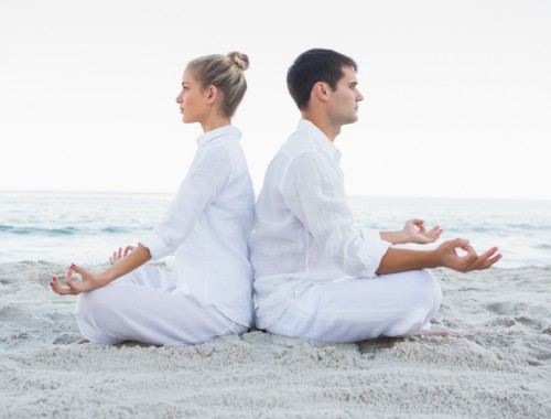 Couple sitting in yoga lotus position back to back on the beach